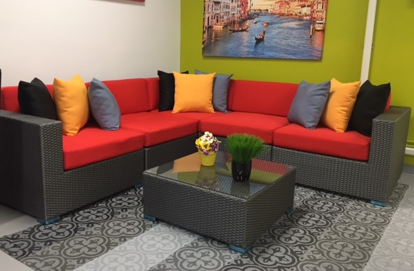 Outdoor Sectional by Vancouver Sofa and Patio, the Kitsilano shown in grey wicker with dark orange cushions