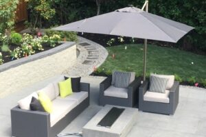 Patio sofa & 2 chairs sitting under a grey umbrella.