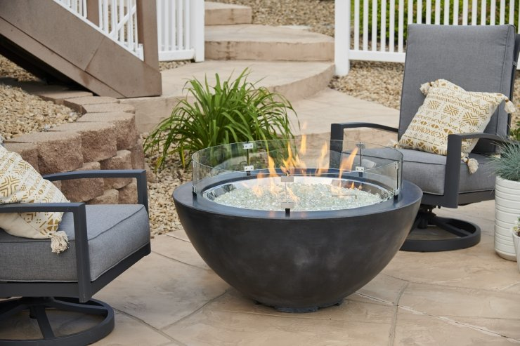 Black Cove 30 fire bowl with flame on and 2 patio chairs.