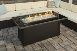 Monte Carlo fire table with flames on by a patio sectional.