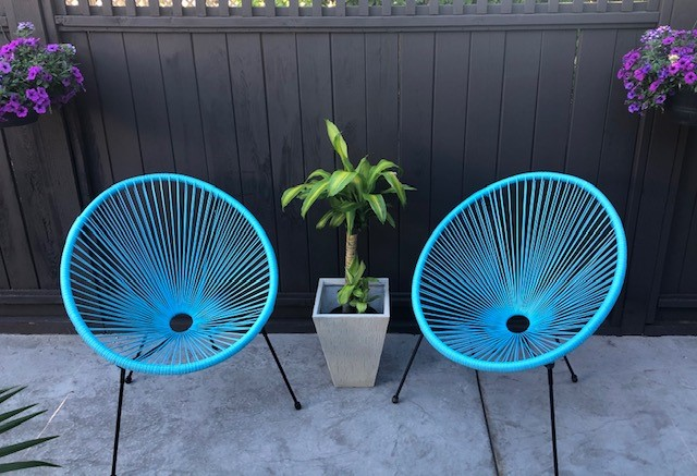 2 blue colored Acapulco chairs with a plant between them.