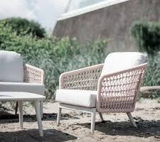 The Poinciana pink collection club chair on a beach.