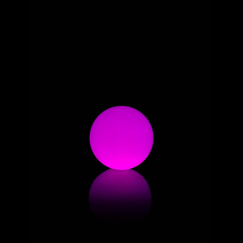 The Bubbles lamp by Vondom lit up a night time in purple.
