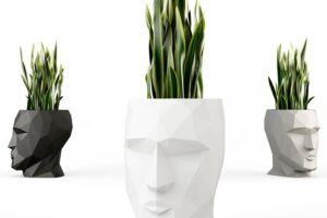 Three Vondom Adan Planters with green plants coming out of their heads.