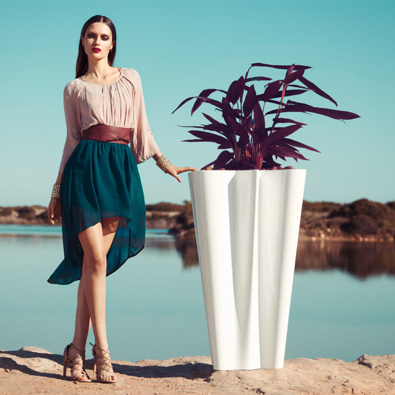 A woman in a green skirt stands next to a Vondom bye bye planter in white with lake in background.