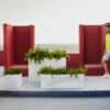 Different sized faz wall planter by Vondom in white with green planters and red patio chairs in background.