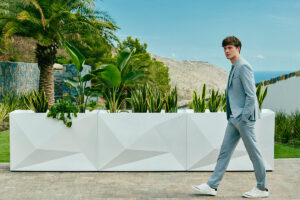 A man walks past 3 white Faz wall planters by Vondom with green plants in them.