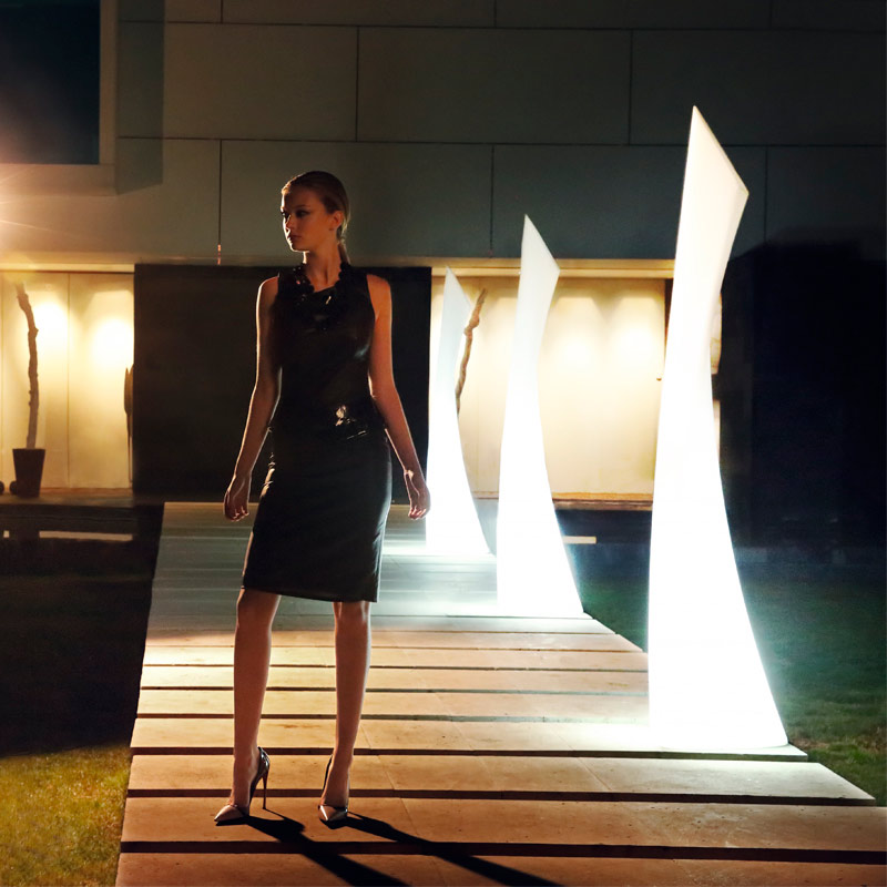 The wing lamp by Vondom lit up with a woman standing next to them.
