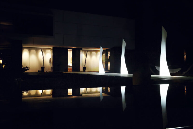 Three Wing Lamps by Vondom, lit up at night time.